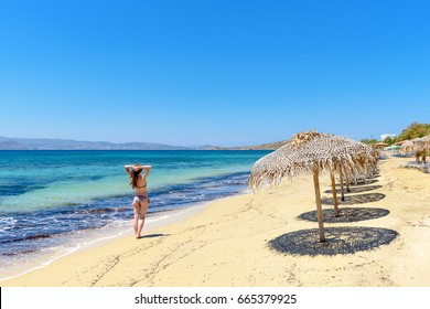 Beautiful young and happy woman having a good time on a summer beach. Agia Anna beach. Naxos, Cyclades Islands, Greece.