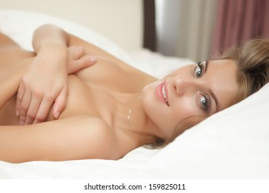 Beautiful young happy woman in lingerie on a white bed interior