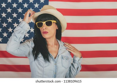 Beautiful young happy woman on American flag background