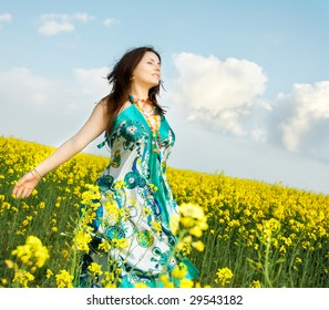 beautiful young happy woman on rapeseed field in bloom