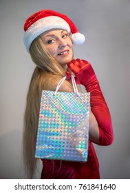 Beautiful young happy woman wearing santa claus dress on white background,and Christmas hat holding gift boxes. Christmas shopping concept