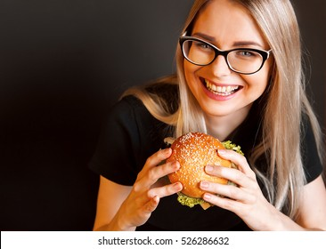beautiful young, healthy girl holds a tasty big burger with beef cutlet. the concept of nourishing food.