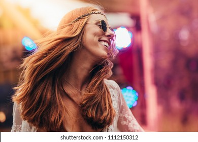 Beautiful young hippie woman enjoying at music festival outdoors. Woman in retro look dancing at music festival.