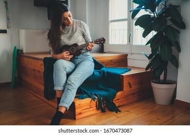 Hermosa joven hipster con ropa informal aprendiendo a tocar guitarra ukulele sentada en las escaleras de madera en casa, joven mujer principiante tocando ukulele, pasatiempo Aprendizaje horario