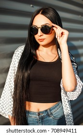 Beautiful young hipster girl with round sunglasses nice fashionable clothes on a sunny day outdoors