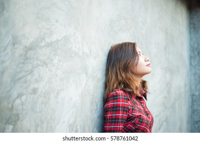Beautiful young hipster standing in a trendy clothes on a grunge background.