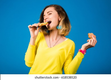 beautiful young hipster woman, eating cookies, smiling, happy, yellow shirt, blue studio background, positive emotion, holding biscuits in hands, sweet food