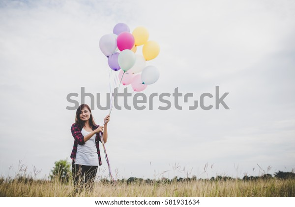 Beautiful young hipster woman holding with colorful of balloons outdoor, Freedom enjoy with nature. Women lifestyle concept.