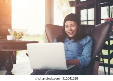 Beautiful young hipster woman sitting with her laptop and coffee in the morning, enjoy and have fun.