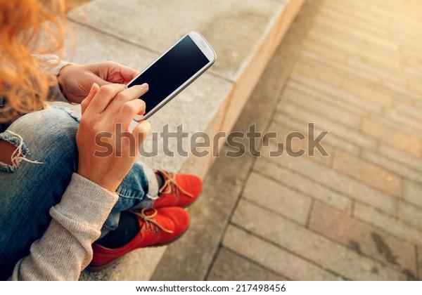 ビーチでスマートフォンを使う美しい若いヒップスター女性