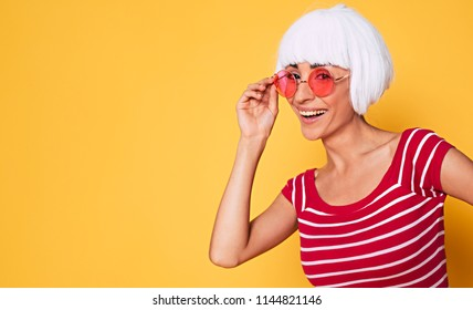 Beautiful young hipster woman wearing blonde wig and pink sunglasses posing against orange background