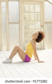 Beautiful young Hispanic model wearing casual exercise clothing stretching in sunny workout room.
