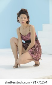 Beautiful young Hispanic model wearing party dress on porch of home on sunny day.