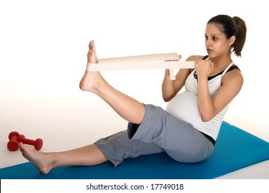 Beautiful young, Hispanic woman in a fitness workout to keep herself physically fit during her pregnancy.  Shot on white background.