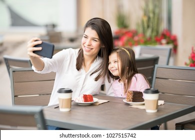 Beautiful young hispanic woman with her little daughter taking selfie with smartphone while sitting at a restaurant