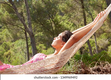 Beautiful young hispanic woman relaxing on hammock in wild forest sunny nature, outdoors. Healthy wellness serenity, spa retreat lifestyle, enjyoing summer holiday, eyes closed in exterior.