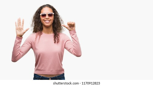 Beautiful young hispanic woman wearing sunglasses showing and pointing up with fingers number six while smiling confident and happy.