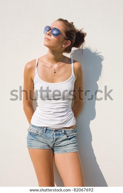 Beautiful young hot brunette posing in hot summer sunshine.