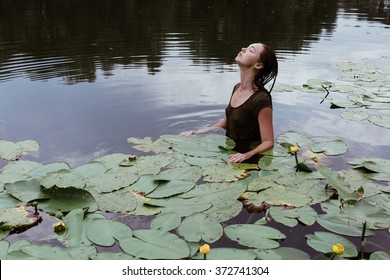 beautiful young hot model girl swimming in the lake full of water lilies during hot summer day