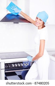 beautiful young housewife cleaning the kitchen hood at home