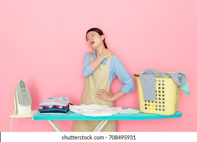 beautiful young housewife doing many housekeep feeling tired and preparing to iron clothing getting shoulder painful isolated on pink background.