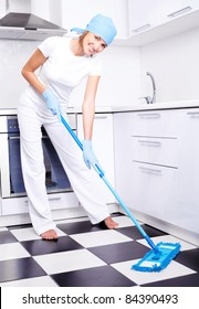 beautiful young housewife with a mop in the kitchen