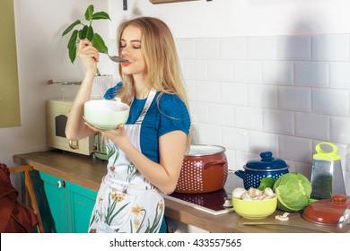 beautiful young housewife tasting the fresh hot soup horizontal photo