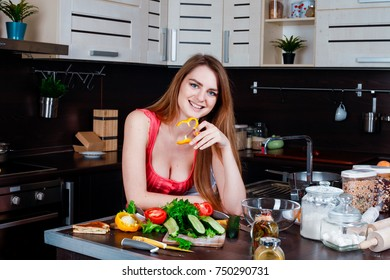 Beautiful young housewife in traditional clothes preparing dinner in the kitchen