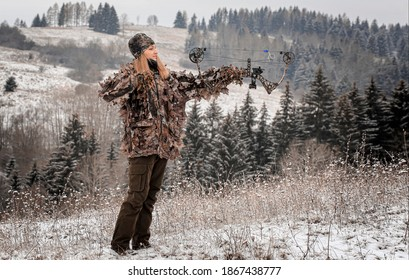 A beautiful young hunter woman in winter landscape on the hunt with hunting bow after shooting with an arrow. She wear  camouflage clothing.