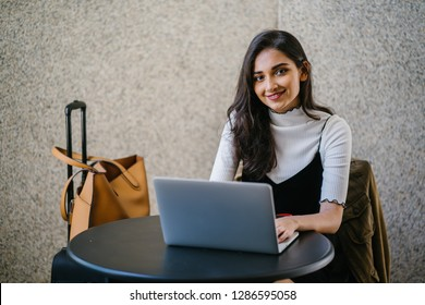 A beautiful and young Indian Asian woman in a turtleneck top and dress is working on her laptop as she sits in a cafe during the day. She has a luggage bag next to her and is smiling.