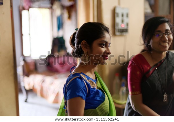 Beautiful and young Indian Bengali sisters or friends in traditional sari are having a good time at home. Indian lifestyle