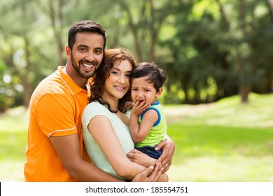 beautiful young indian family outdoors looking at the camera