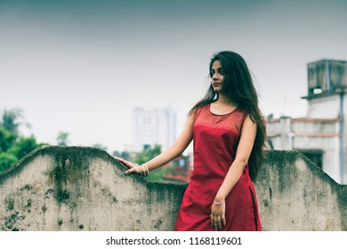 Beautiful and young Indian girl with traditional Indian salwar suit dress is standing on rooftop leaning on the boundary wall. Indian dress and lifestyle.