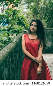 Beautiful and young Indian girl with traditional Indian salwar suit dress is standing in nature. Indian dress and lifestyle.