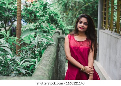 Beautiful and young Indian girl with traditional Indian salwar suit dress is standing in a green park. Indian dress and lifestyle.