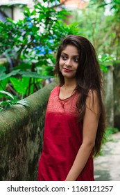 Beautiful and young Indian girl with traditional Indian salwar suit dress is standing in a green environmental background. Indian dress and lifestyle.