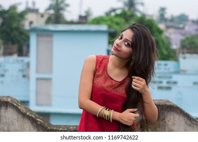 Beautiful and young Indian girl with traditional Indian salwar suit dress is making her hair while standing on rooftop. Indian dress and lifestyle.