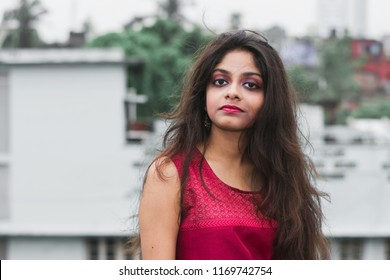 Beautiful and young Indian girl with traditional Indian salwar suit dress is standing on rooftop. Indian dress and lifestyle.