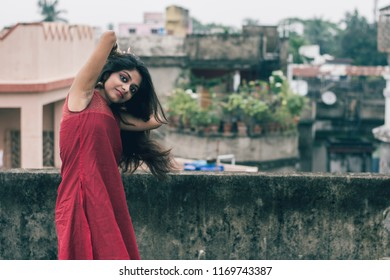 Beautiful and young Indian girl with traditional Indian salwar suit dress is standing on rooftop leaning on the boundary wall with one hand over her head. Indian dress and lifestyle.