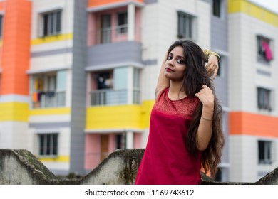 Beautiful and young Indian girl with traditional Indian salwar suit dress is standing on rooftop with one hand over her head with a colorful building in her back. Indian dress and lifestyle.