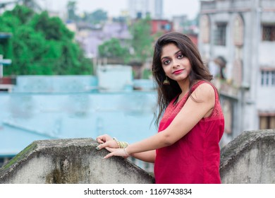 Beautiful and young Indian girl with traditional Indian salwar suit dress is standing on rooftop leaning on the boundary wall with a posing style. Indian dress and lifestyle.