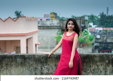 Beautiful and young Indian girl with traditional Indian salwar suit dress is standing on rooftop with an elegant style. Indian dress and lifestyle.