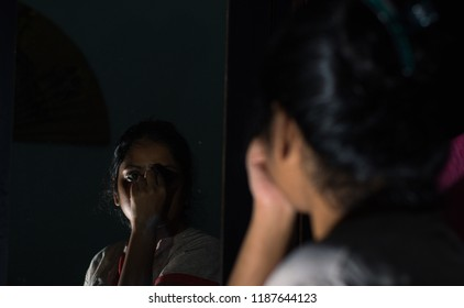 A beautiful and young Indian married woman is wearing sindoor in front of a mirror in light and shadows. Indian lifestyle and culture