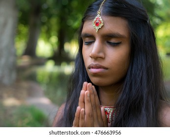 Beautiful young indian woman praying in the park. Hinduism | religion | spirituality concept