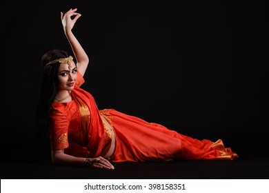 Beautiful Young Indian Woman in red Traditional Clothing with perfect Makeup and Oriental Jewelry. Beautiful Girl Bollywood dancer (Bellydancer) in Sari. Eastern fairy tale