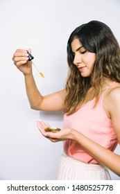 Beautiful young Indian woman squeezing drops of oil facial serum into gold dish