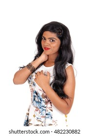 A beautiful young Indian woman standing in a summer dress with longblack hair, isolated for white background.