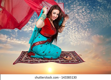 Beautiful young indian woman in traditional clothing sitting on a flying carpet