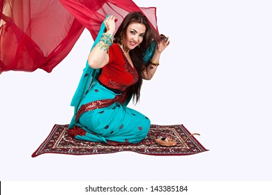 Beautiful young indian woman in traditional clothing sitting on a flying carpet, isolated on white
