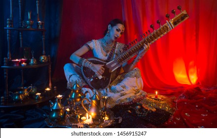 Beautiful young indian woman in traditional Sari clothing with Oriental Jewelry Playing the Sitar. Indian woman Playing night Raga the Sitar, Eastern Music. Musical Candlelight Party in India.